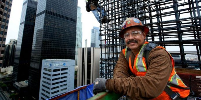 Working 300 feet above downtown Los Angeles, ironworkers position reinforcing steel onto the walls of the New Wilshire Grand.