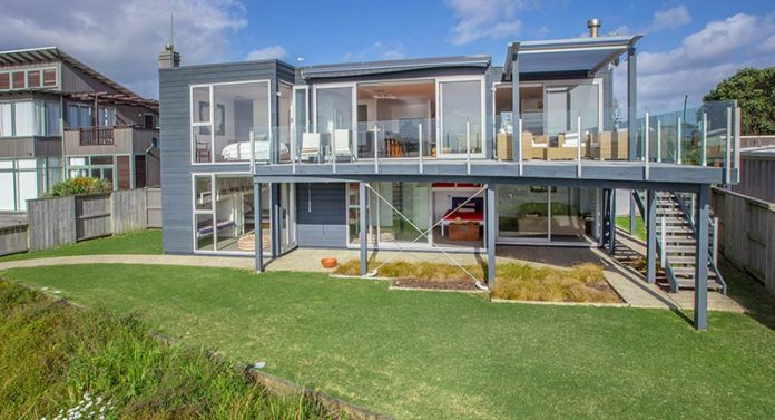 A home on Omaha Beach, north of Auckland, illustrates the kind of modern design and top-end construction now common among vacation homes, popularly called baches
