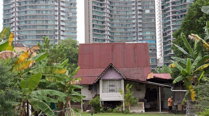 A traditional Malay house in Kampong Bharu, overshadowed by high-rise apartment towers