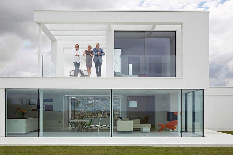 Host Kevin McCloud, right, with Rob Hodgson and Kay Ralph at their cliffside house in Wales