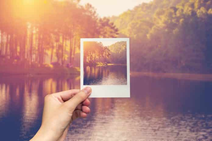 hand hold instant photo Pond water and sunrise with vintage effect.