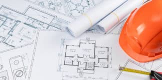 Orange helmet, pencil, architectural construction drawings, tape measure. The concept of architecture, construction, engineering, design. Copy space.