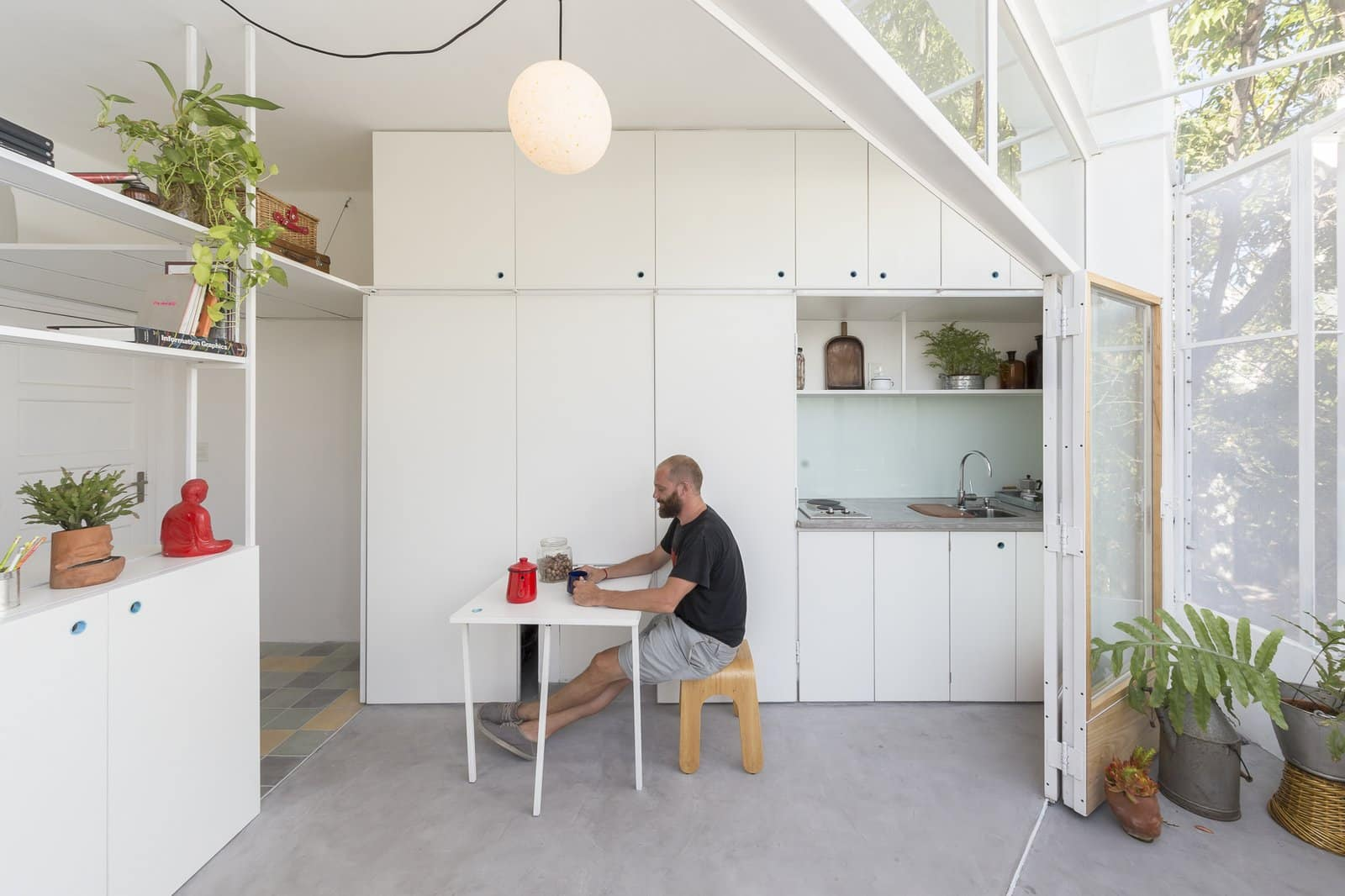 A pull out dining table is concealed behind one of the white kitchen panels1