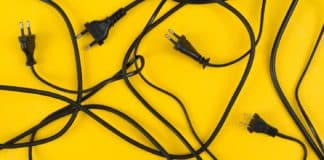 Messy of electrical cords and wires unconnected on colorful top view background, messy electric equipment flat lay concept.