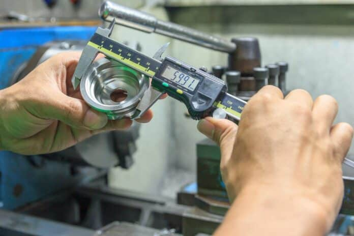 Measure the size of the metal parts with a Electronic digital caliper measuring device for control specification of metal parts. Shop metalworking plant.