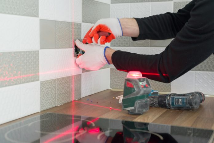 Electrician using infrared laser level to install electrical outlets. Renovation and construction in kitchen.