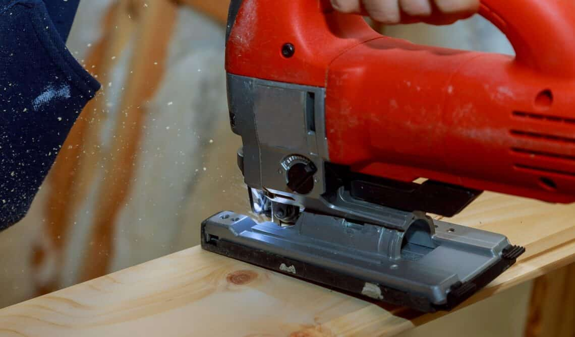 Close up electric jigsaw cutting a piece of wood, electric hand tools