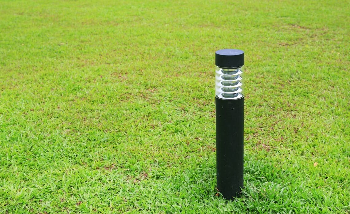 Close up pole of lamp in green grass field.