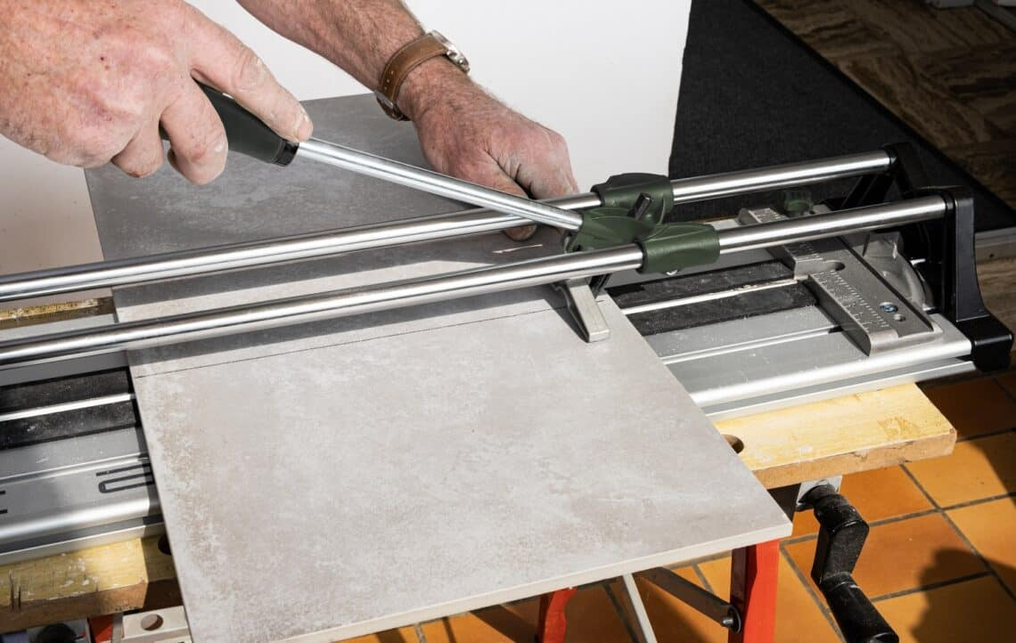 the mason cuts a ceramic tile with a tile cutter