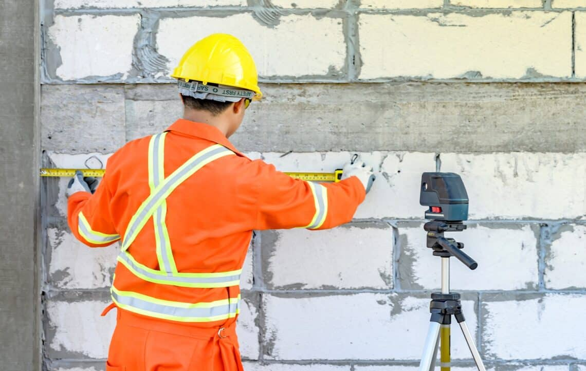 Construction workers Is using a laser level meter for wall leveling device