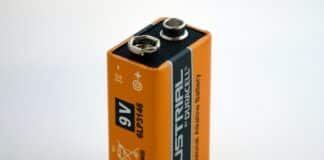 auto mechanic check car battery voltage by voltmeter multimeter at repair service station