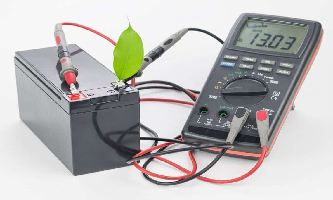 Rechargeable battery with connected measuring instrument and green leaf. The concept of clean energy.