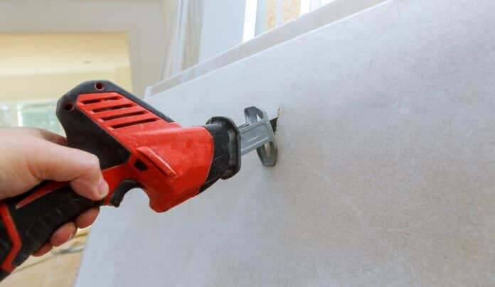 Plasterboard cutting of drywall hand with grunge dirty saw