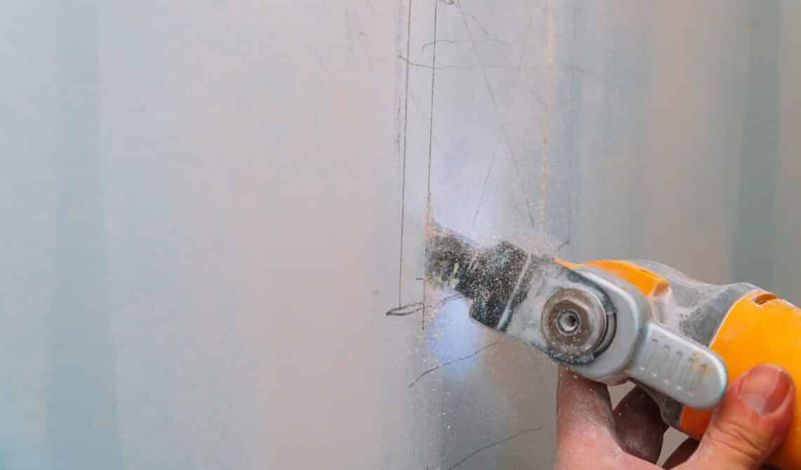 Construction worker cutting gypsum drywall by using electric cutter angle grinder