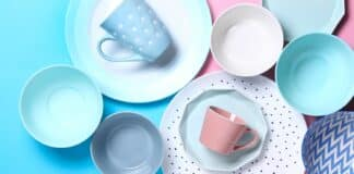 Empty ceramic tableware. Ceramic plates and cups on yellow and blue background. Overview empty food table with tableware. Set of different modern white and blue plates,bowls and cups.Top view, flat lay.Copy space.