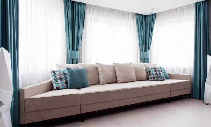 Large modern couch in the room near a big window, light and turquoise tones