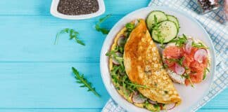 Breakfast. Omelette with radish, green arugula and sandwich with salmon on white plate. Frittata - italian omelet. Banner. Top view