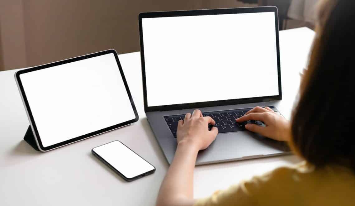 Yellow shirt woman using laptop and tablet, phone placed on the table, mock up of blank screen.