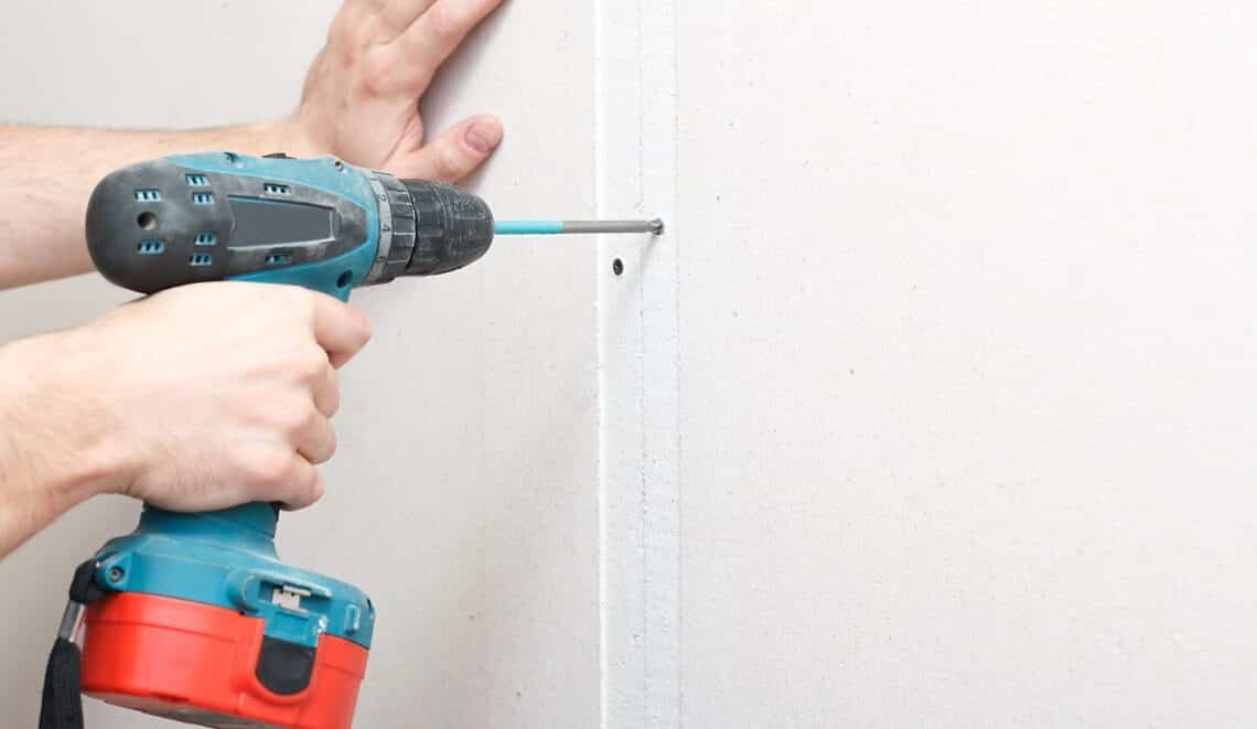 a man with a screwdriver in his hand fastens drywall to the wall