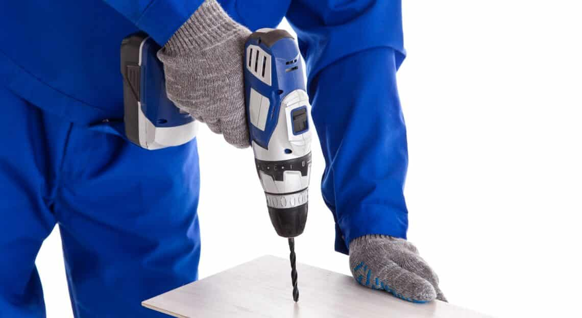 Worker in blue uniform using battery screwdriver, isolated on white