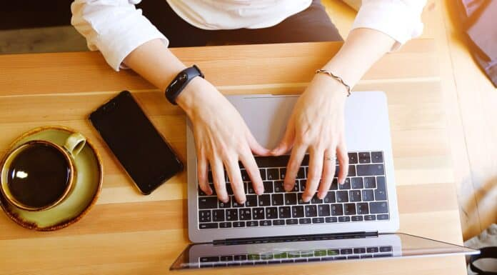 Female entrepreneur Manager using her laptop , working in a cafe or office. Near mobile phone and coffee. Freelance workplace, Breakfast business lady. Search for information on the Internet.