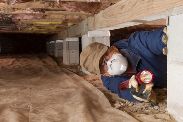 Termite inspector in residential crawl space inspects a pier for termites.