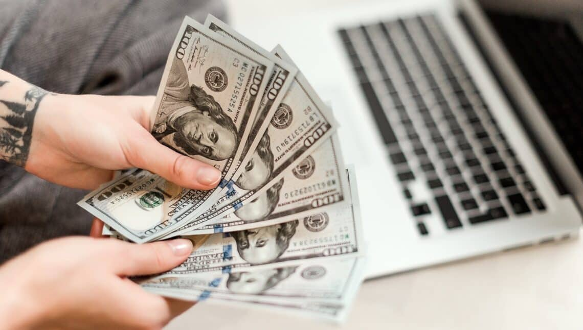 Freelance work concept - close up of woman hands holding new dollar bills she earned working from laptop at home online