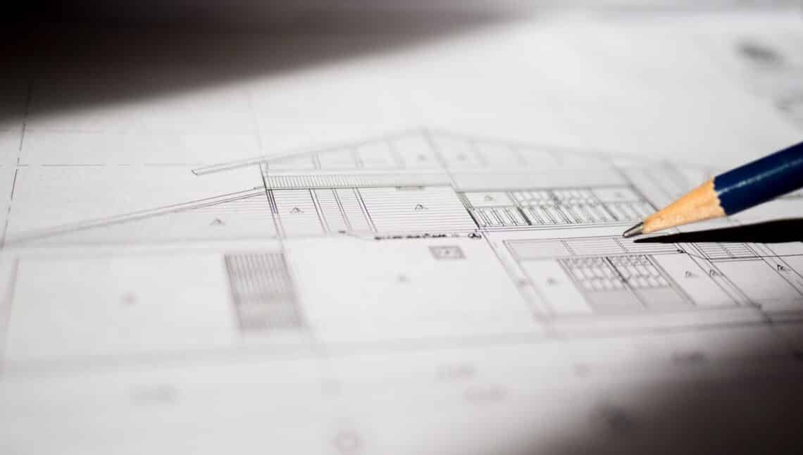 Construction plans and pencil for drawing on blueprint with sunlight from windows
