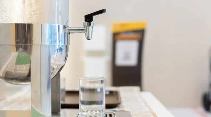 close up dispenser cooler drink water cold fresh. water droplets in water glass. blur foreground.