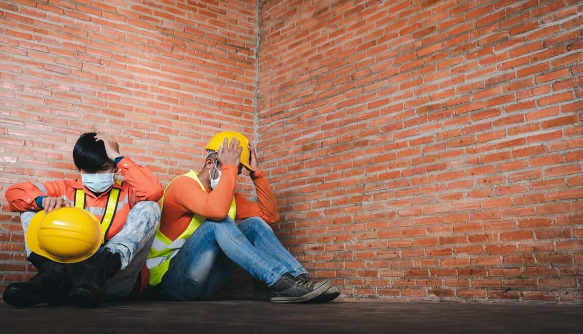 Two construction workers regret sitting sad at the job site Wearing a medical mask to prevent Covid-19 is unemployment and the economic crisis. Unemployment Failed During Covid-19