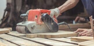 Carpenter sanding wood with belt sander at workshop in wooden cutting board project or woodworking carpentry