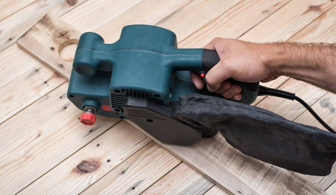 Electric belt sander, sanding machine in male hand. Processing of workpiece on light brown wooden table. Close up.