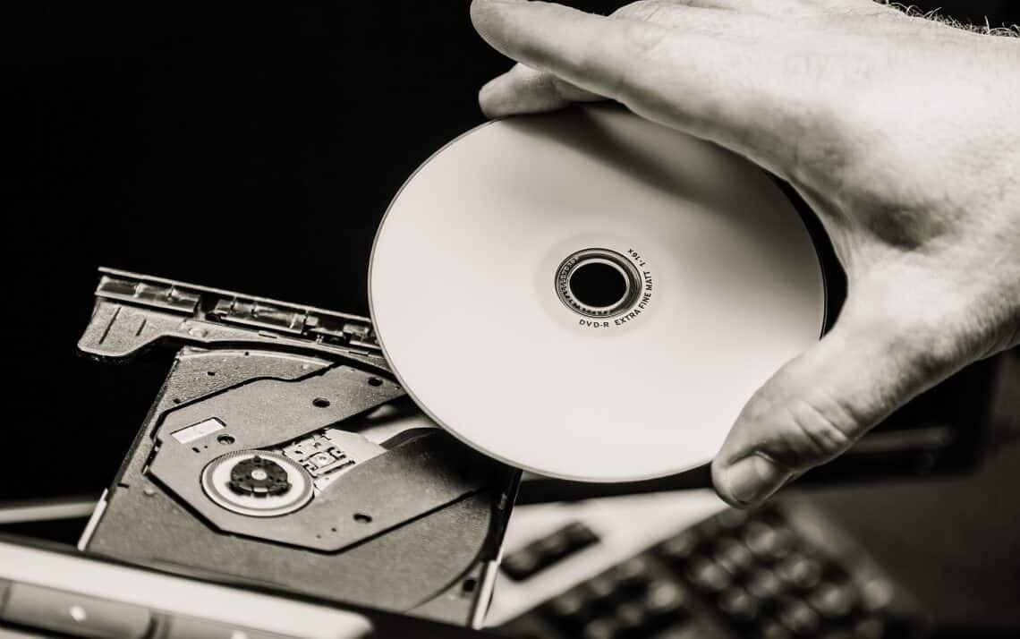 Male hand inserting a DVD into a disk drive. Black and white.