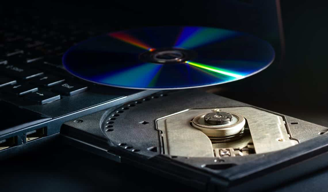 Cd on the computer notebook cd rom in darkness. Concept of technological advances in computer data recording systems.