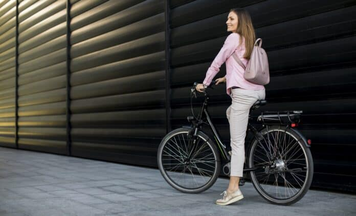 Pretty young woman riding an electric bicycle in urban environment