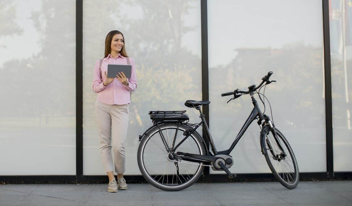 Pretty young woman standing by an electric bicycle and using digital tablet in urban environment