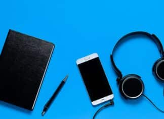 Mobile Phone, Headphones, Notepad And Pen On A Blue Background