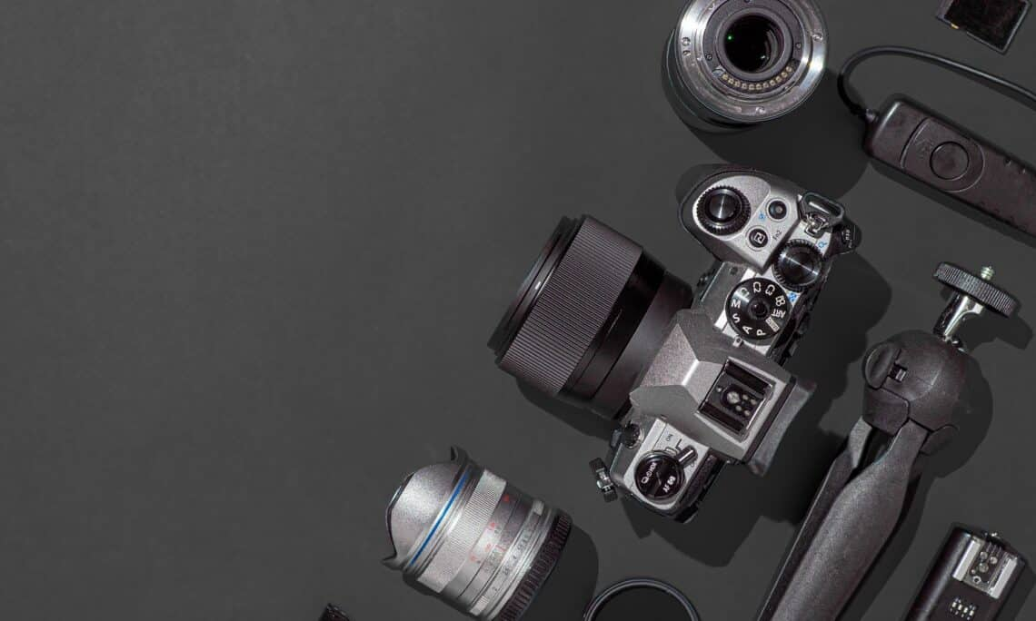 Photographer workplace with dslr camera, lens, pen tablet and camera accessories on black background. Camera, photography, visual content concept. Flat lay or top view. Copy space. Hard light.