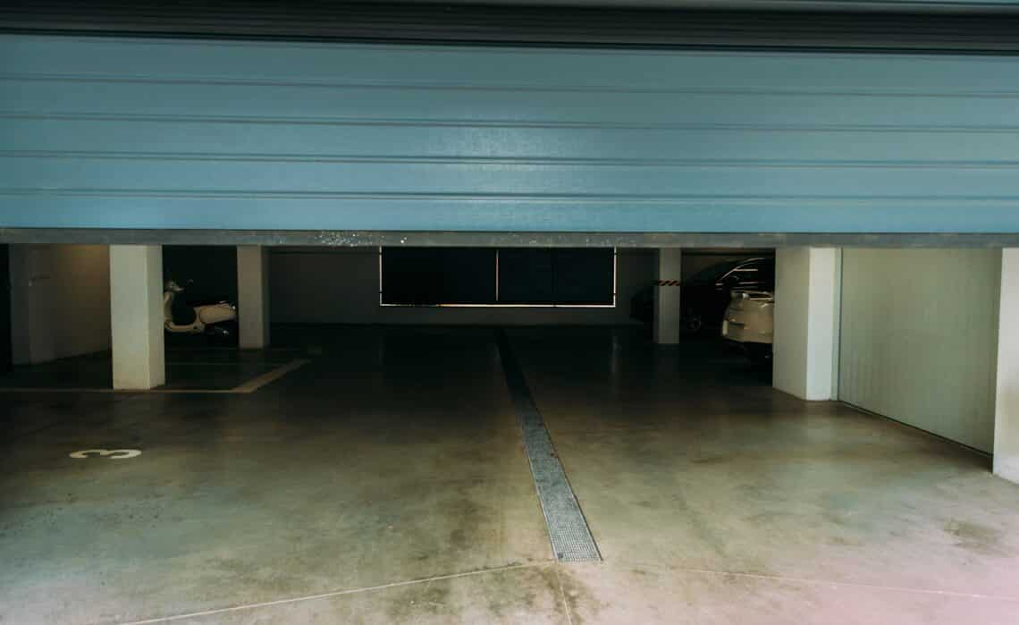 Photo of an automatic closing blue pvc door of a garage with a remote controller.