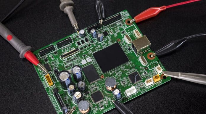 Close-up of electronic circuit board with several microchips with tools and wires around