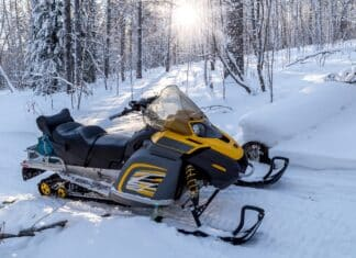 A yellow snowmobile stands on a trail in a winter forest.