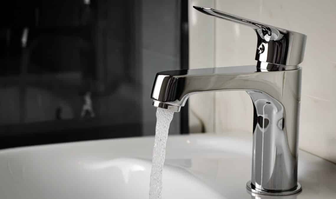 Water flows from the tap or faucet in bathroom. Copy space, close up