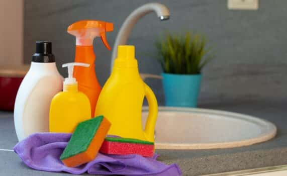 Household chemicals product bottles standing near the kitchen sink close up