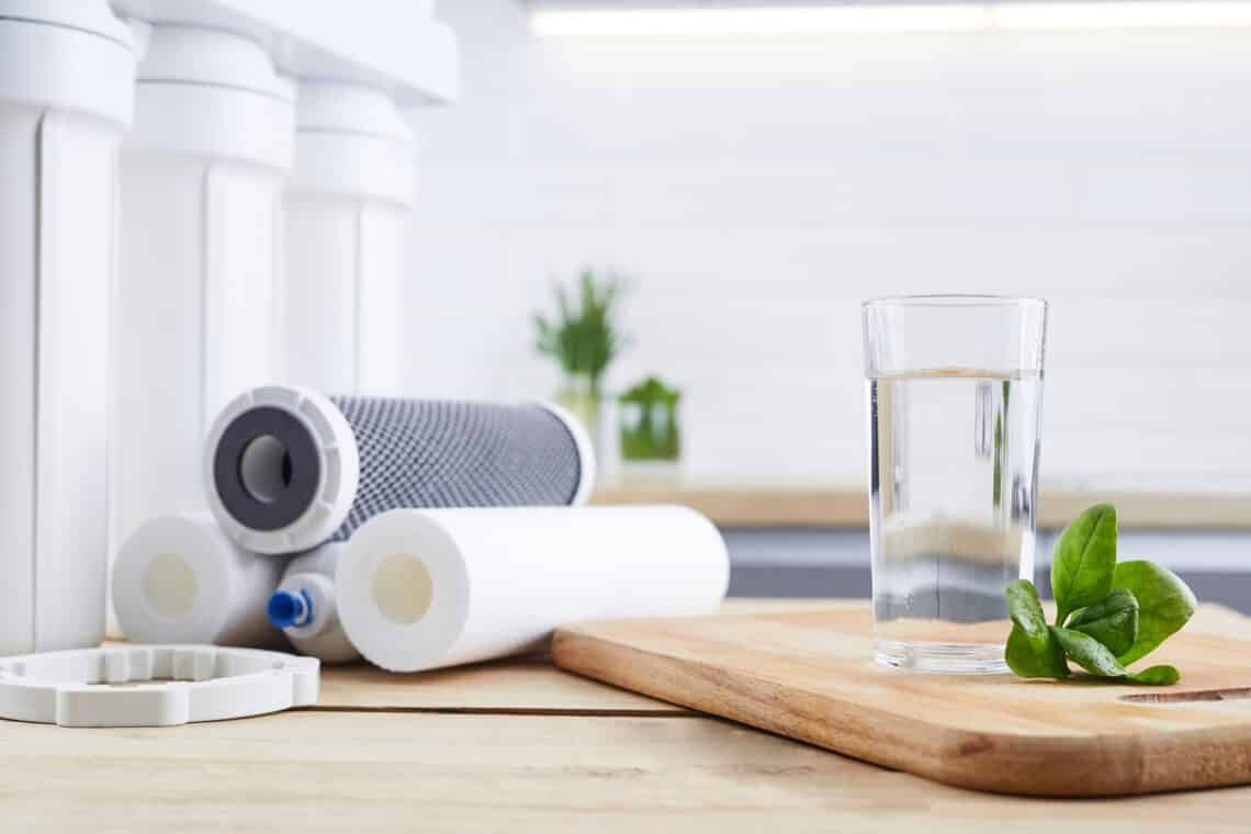 A glass of clean water with osmosis filter, green leaves and cartridges on wooden table in kitchen interior. Concept Household filtration system.