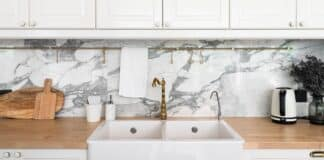 Modern classic kitchen interior with kitchen appliances and white ceramic sink with gold mirror faucet on wood top with marble wall in the background / kitchen interior