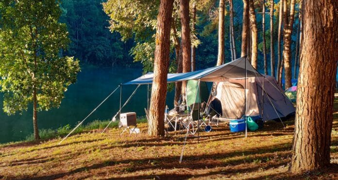 Camping tent with equipment outdoor lifestyle.Morning sunlight with Big Camping tent near river.
