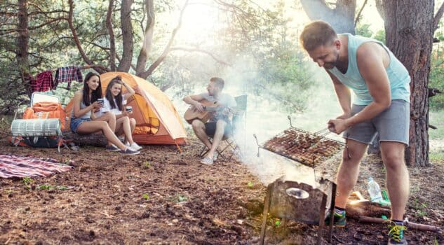 Party, camping of men and women group at forest. They relaxing, singing a song and cooking barbecue against green grass. The vacation, summer, adventure, lifestyle, picnic concept