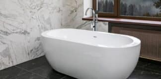 Luxury apartment bathroom with standalone ceramic bath, marble walls and panoramic window with forest valley view