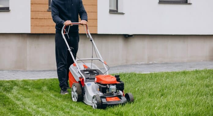 Man cutting grass with lawn mover in the back yard