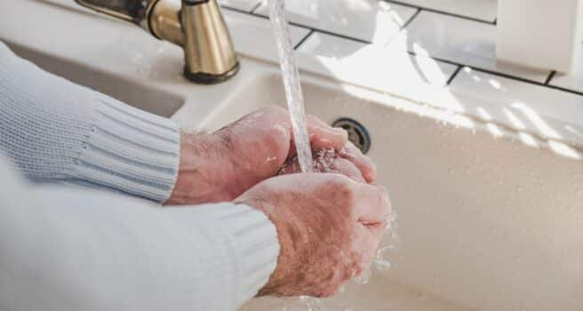 Men's hands and a bar of soap on a background of a vintage tap. Top view, closeup. Health Care and Prevention Concept
